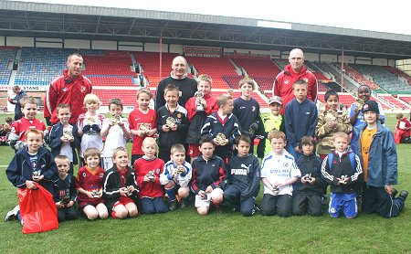 Swindon Town manager Maurice Malpas with youngsters from the Community Football initiative