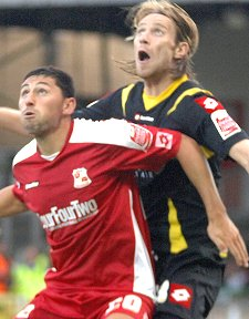 Swindon Town's Billy Paynter with QPR's Kaspars Gorkss
