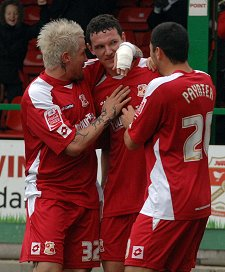 Sean Morrison is congratulated by Lee Peacock and Billy Paynter after the 17-year-old put Swindon one-nil up