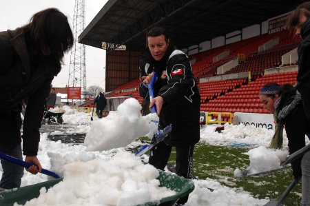 Danny Wilson Swindon Town Manager clearing the snow at the football club